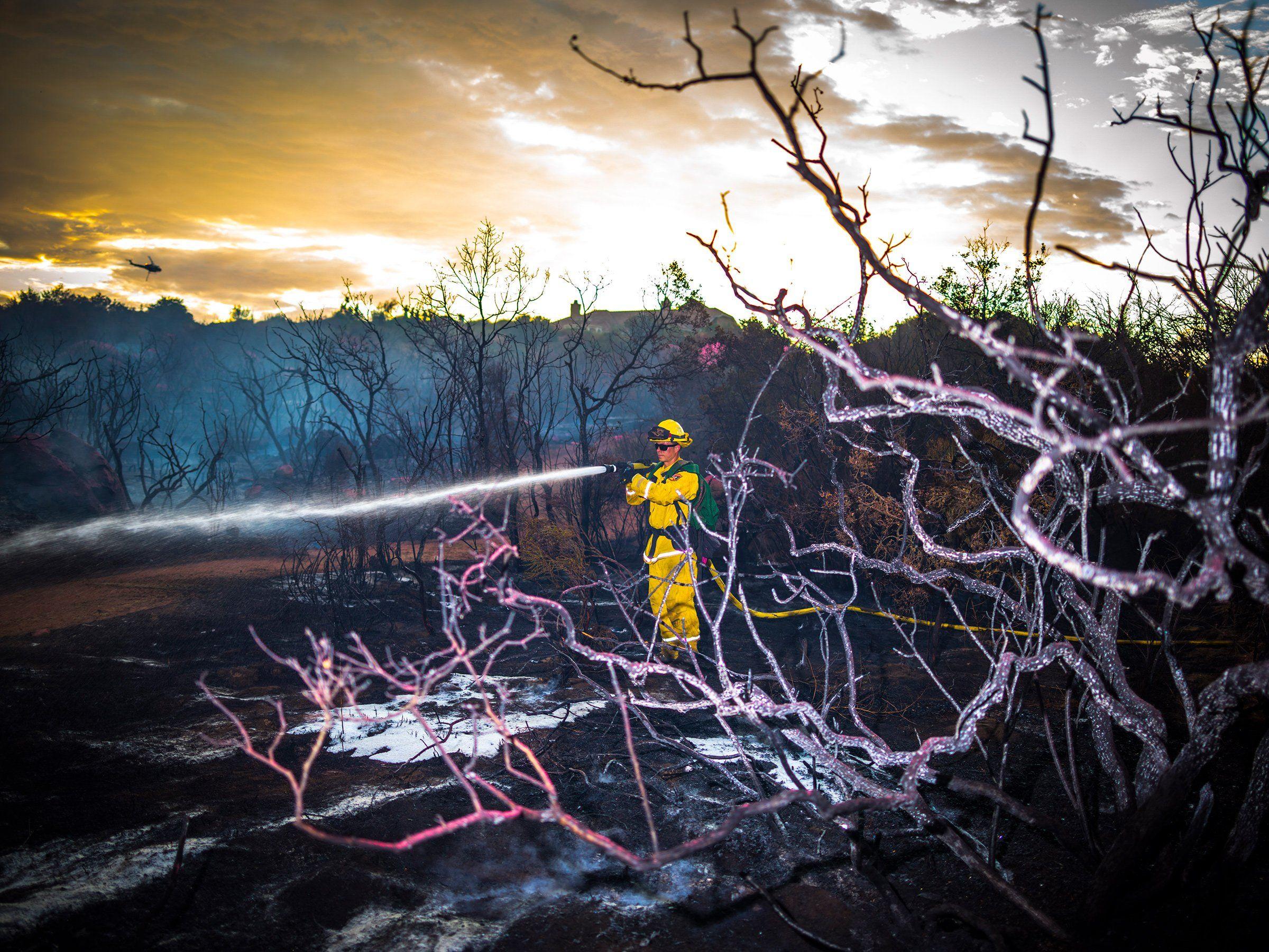 A firefighter extinguishes hotspots near the origin of the Tenaja Fire near Murrieta, Calif., on Sept. 5.
