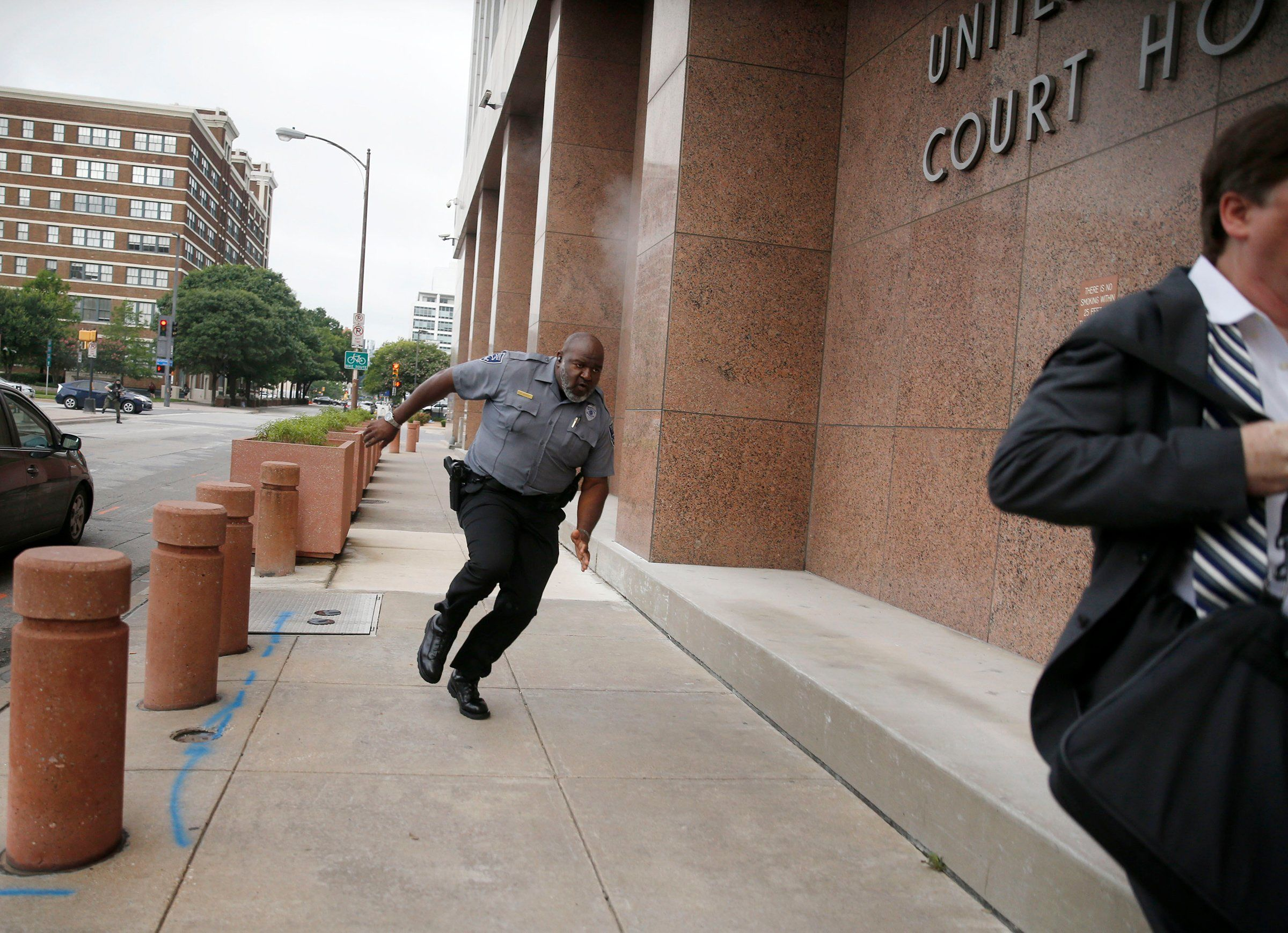 A security guard and a man run for cover as bullets ricochet off the Earle Cabell Federal Building as a shooter (at left, far background) fires towards them in Dallas on June 17.