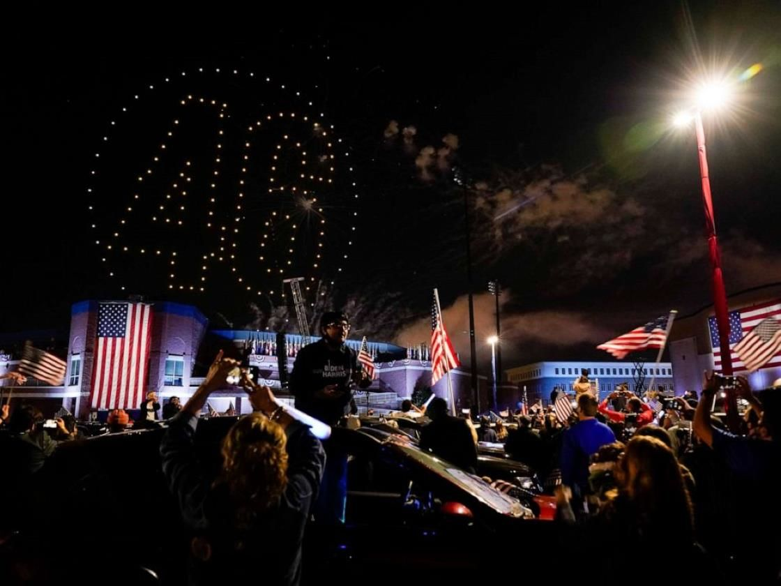 a group of people sitting at night: Drones illuminate the sky with the numbers 46 after an event by President-elect Joe Biden, Saturday, Nov. 7, 2020, in Wilmington, Del.
