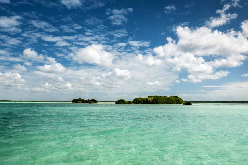 """Slide 11 of 16: Mexico has some gorgeous Caribbean water on its east coast, and Lake Bacalar looks like it's part of it—with beaches, jungle, and mangroves, it's nearly impossible to tell the two locales apart. Yet Lake Bacalar has one big difference: It is actually a freshwater lagoon. Located on the Yucatan peninsula near the Belize border, the lake sits inland from the sea, narrow and long at 26 miles. Fed by a series of underground rivers, its white sand bottom allows the clear water to change color throughout the day, from turquoise to indigo, earning it the vibrant nickname """"lake of seven colors."""" Check out these absolutely stunning places on Mexico's Pacific coast."""