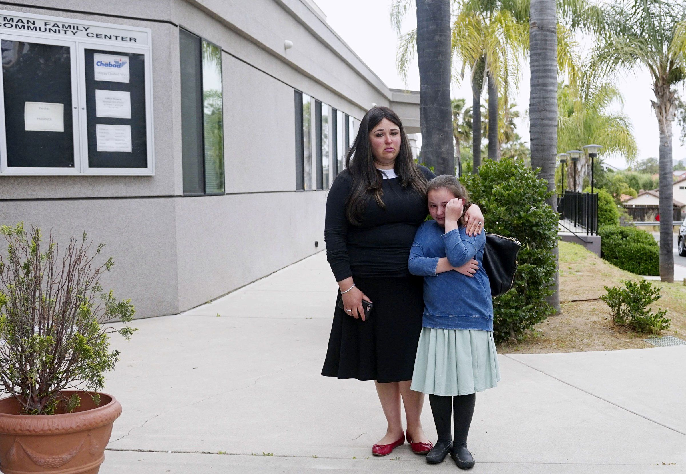 A woman and a young girl, congregants of the Chabad of Poway Synagogue, weep during a news conference on April 28. One person was killed and three people, including a rabbi, were injured at a shooting there a day earlier.