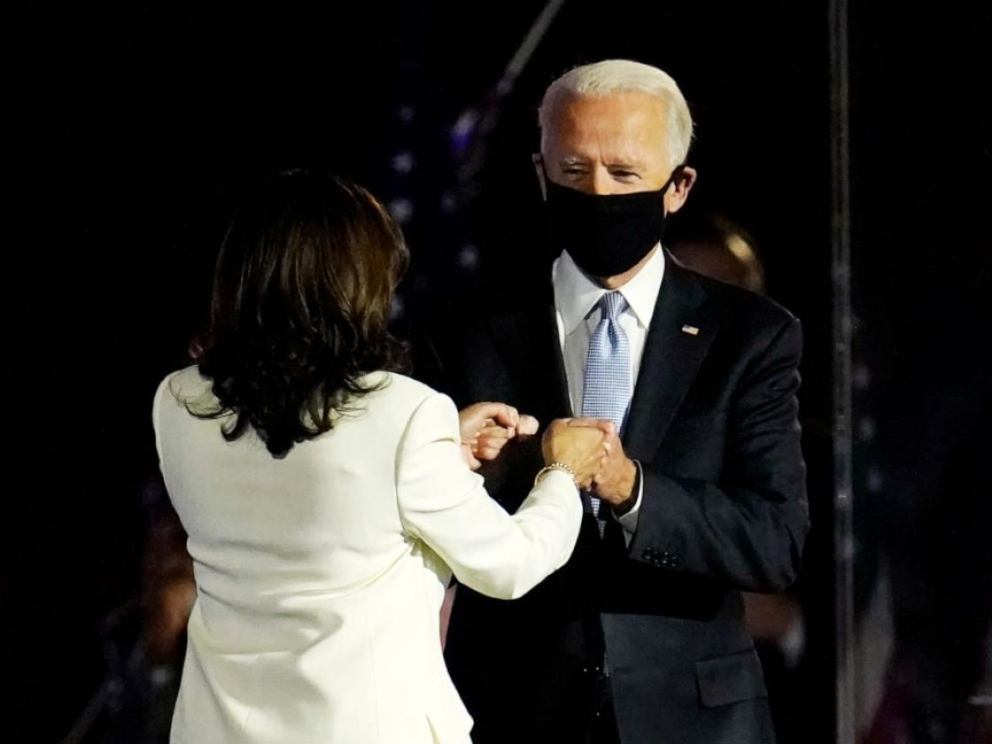 a person wearing a suit and tie: President-elect Joe Biden is greeted on stage by Vice President-elect Kamala Harris before he speaks in Wilmington, Del., Saturday, Nov. 7, 2020.