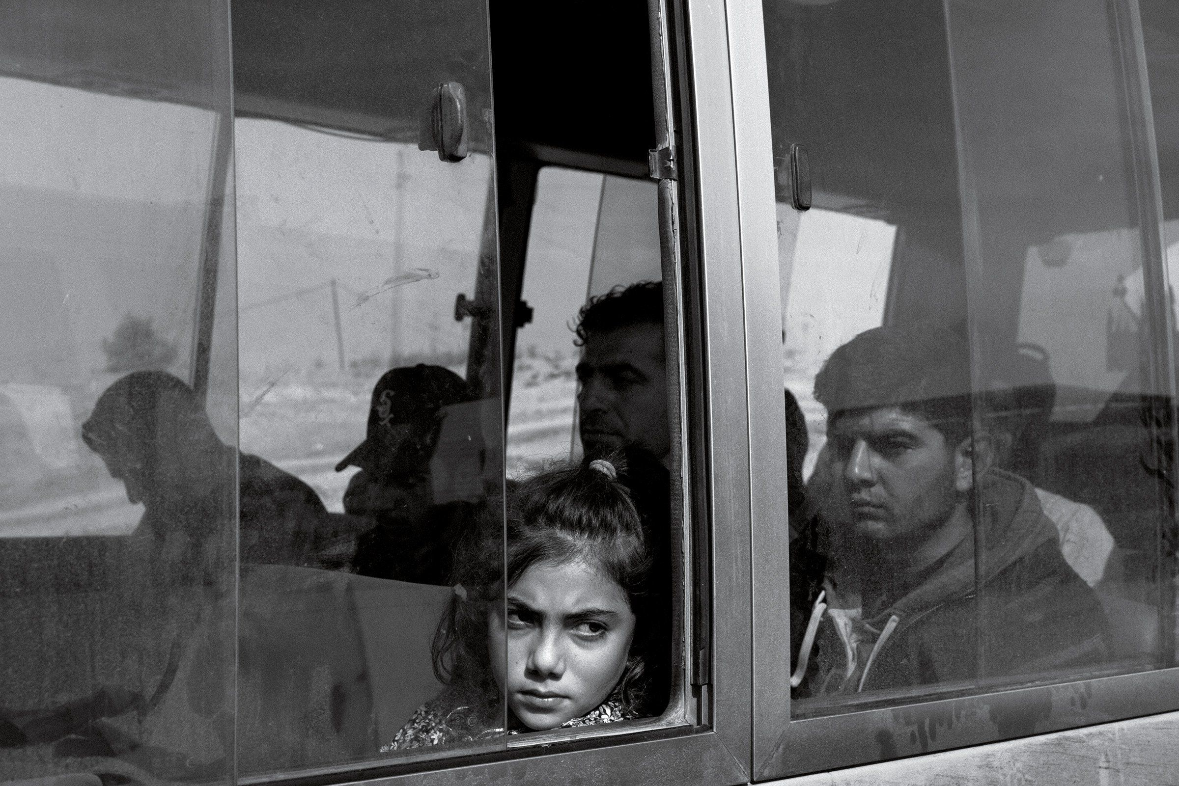 Nuhat Abdul Hamid, 9, from the Syrian Kurdish town of Darbasiyah, aboard a bus transporting refugees to the Bardarash camp in Iraq on Nov. 1.