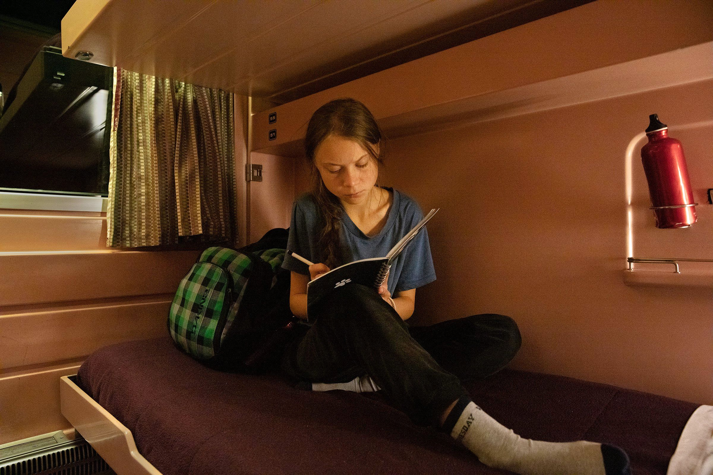 Greta Thunberg writes in her journal on the train as she travels from Lisbon to Madrid for a U.N. climate conference on Dec. 5. Days later, the climate activist was named TIME's 2019 Person of the Year.