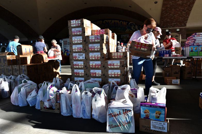 Volunteers prepare groceries to be given out at a drive-thru Three Square Food Bank emergency food distribution site at Boulder Station Hotel & Casino in response to an increase in demand amid the coronavirus pandemic on April 29 in Las Vegas.
