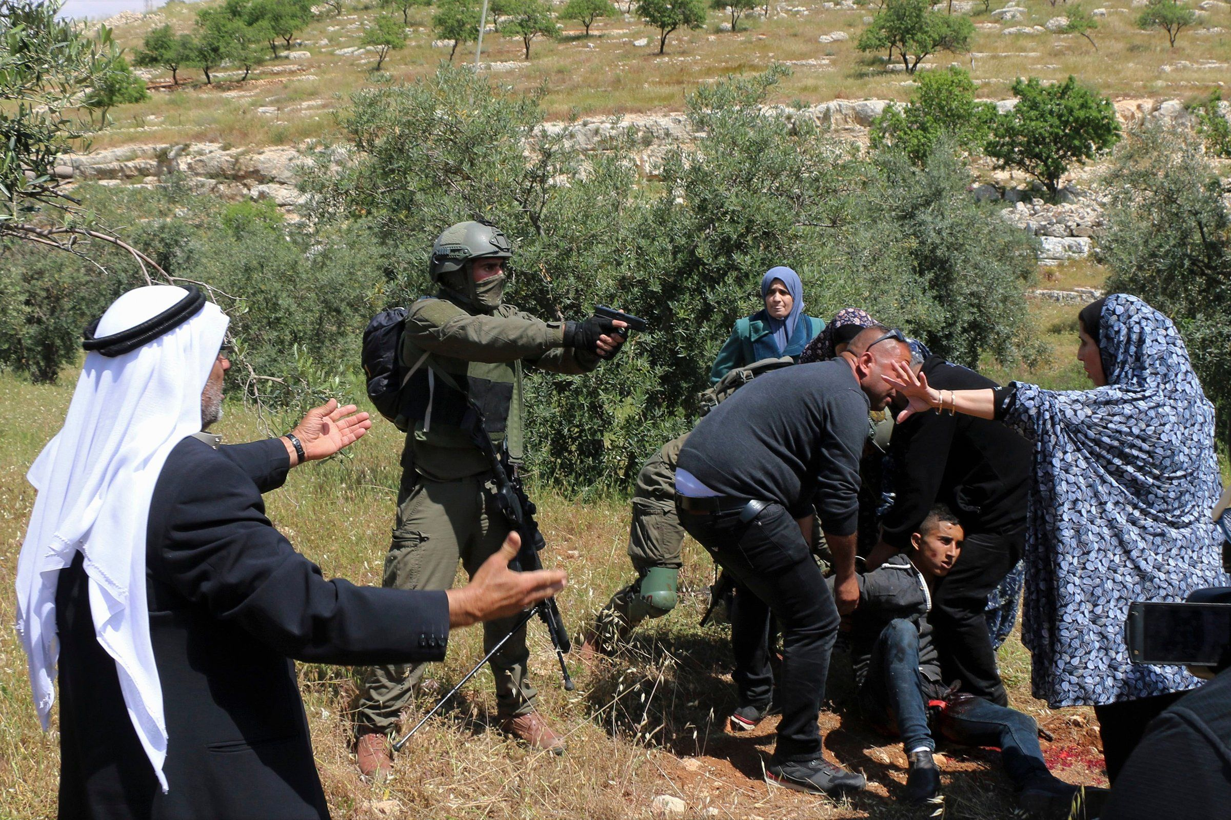 An Israeli soldier points his pistol at a group of Palestinians gathering around a wounded Osama Hajahjeh, 16, near the village of Tekoa, West Bank, in April. Hajahjeh later said he was shot in his legs by Israeli soldiers while he was handcuffed and blindfolded, shortly after being arrested.