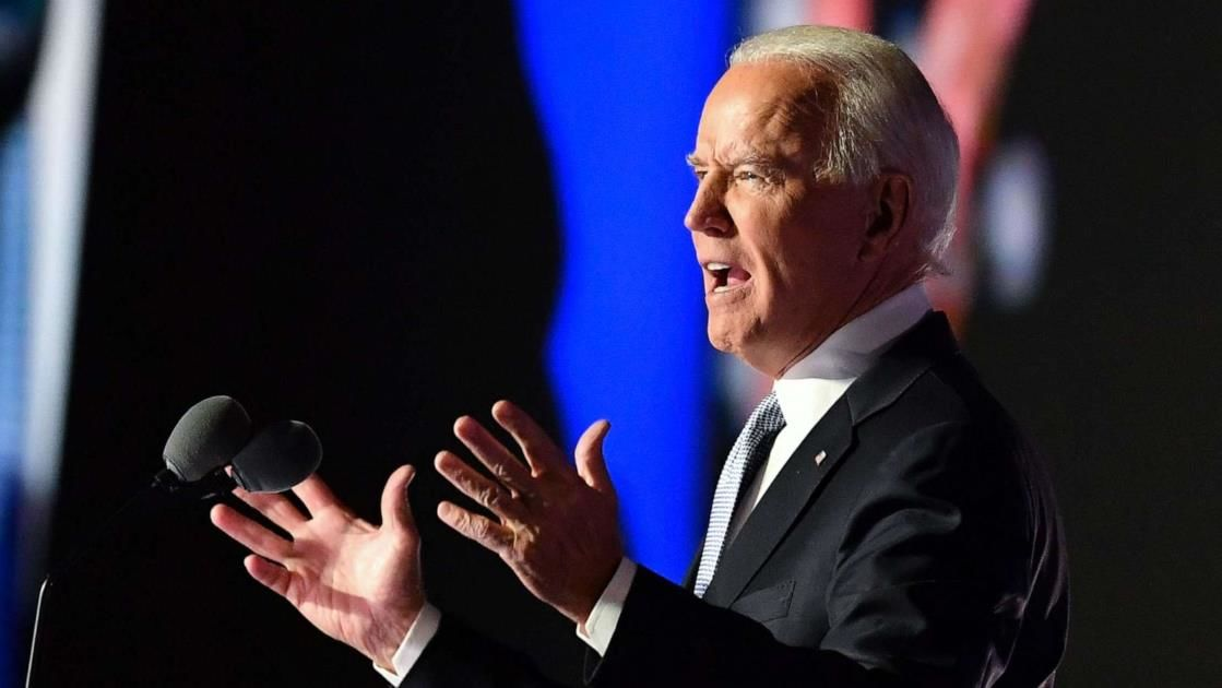 a man wearing a suit and tie talking on a cell phone: President-elect Joe Biden delivers remarks in Wilmington, Del., on Nov. 7, 2020, after being declared the winner of the presidential election by media organizations.