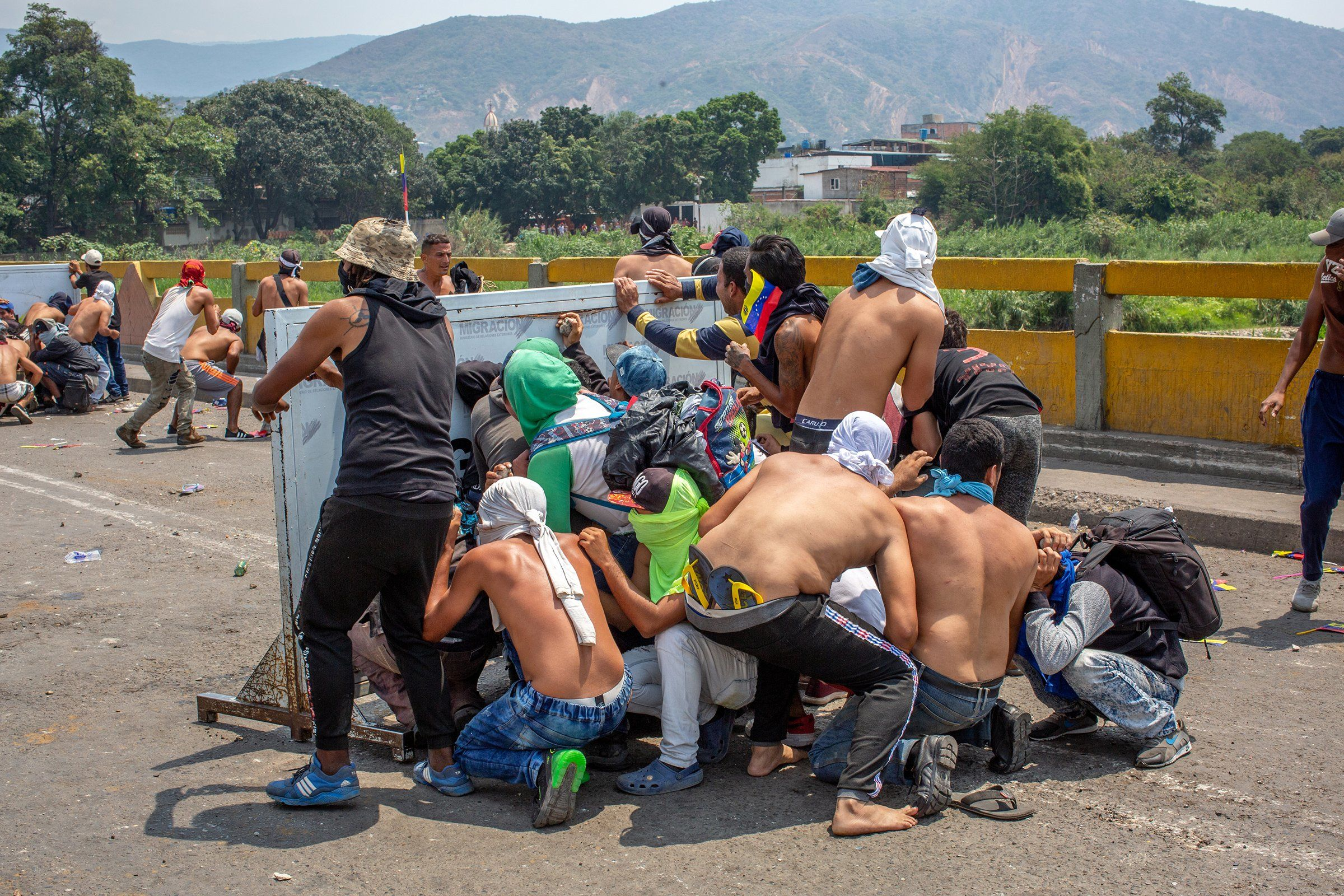 A group of demonstrators take cover during a clash with Venezuelan national police officers on a bridge near Cúcuta, Colombia, on Feb. 23. Clashes along the border stranded aid caravans.